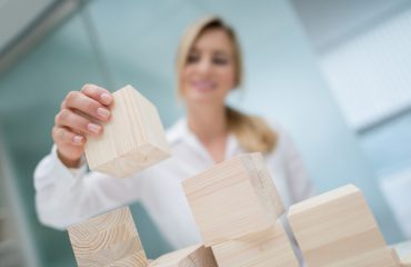 Successful business woman building a project with wooden cubes at the office