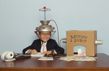 A young boy businessman sitting at a desk records the amount of British Pound Sterling his homemade money machine makes. He is dressed in a suit and pink tie, glasses, and a mind reading helmet on his head. Let's make some money with clever business.